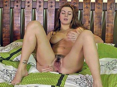 Aroused babe hand-fucking her hairy muff